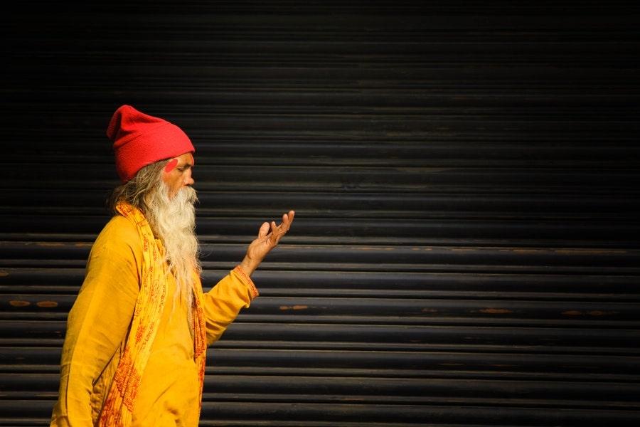 sadhu standing beside roller shutter